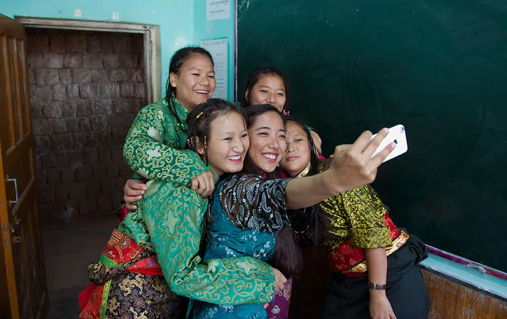 Exile Tibetan school students in traditional attire take a selfie with their instructor, as they wait to perform a song during the Founding Anniversary celebrations of the Tibetan Children's Village School in Dharmsala.