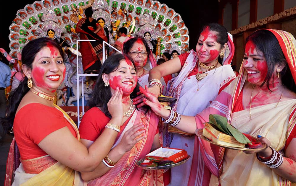 Married Bengali women play with vermilion during Sindur Khela on the last day of Durga Puja in Bhopal.