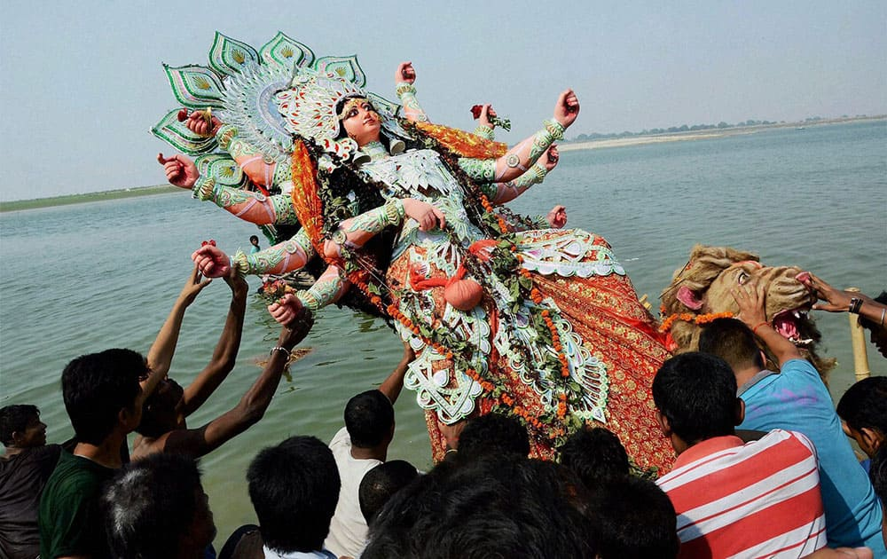 Devotees immerse an idol of goddess Durga on the bank of river Ganga in Patna.