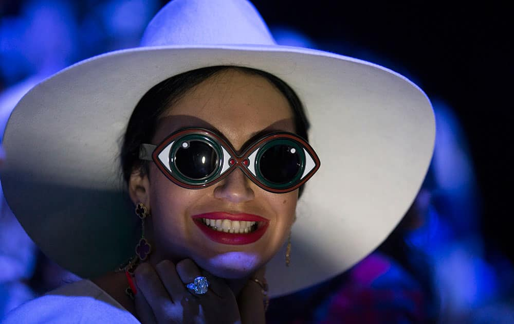 A spectator smiles while watching a model display a creation by Turkish designer Tarik Ediz during Fashion Week in Moscow, Russia.