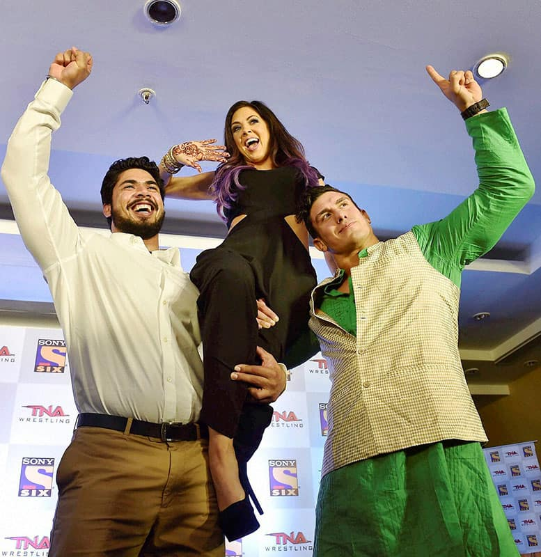 Wrestler Mahabali Shera (L), woman wrestler Rebel and Ethan Carter III (R) pose during a press conference to announce the partenership of Sports Chanel Sony Six and TNA wrestling to host the 1st ever Live International televised wrestling event in Bengaluru.