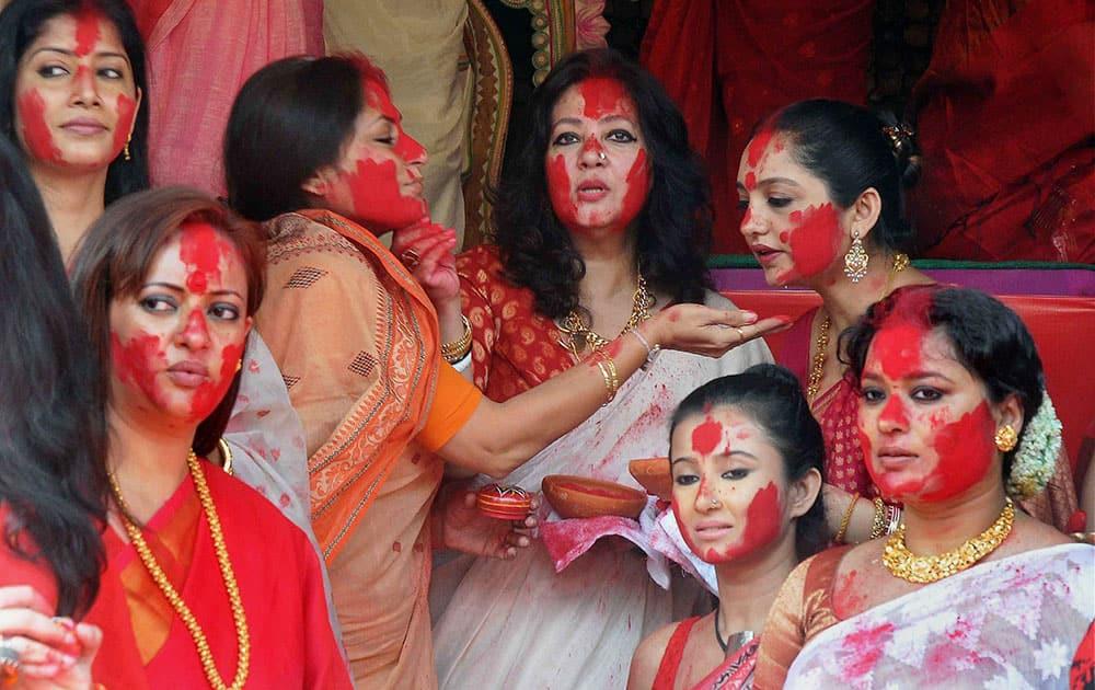 Bengali film actress & Trinamool Congress MP Moon Moon Sen(C) participate in Sindur Khela with film actress & BJP leader Rupa Ganguly and others during Vijaya Dashami celebrations, at Chalta Bagan Sarbojanin in Kolkata.