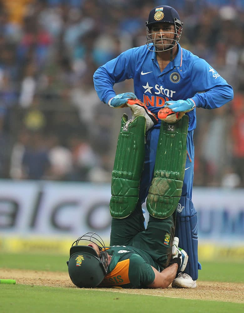 India's captain Mahindra Singh Dhoni, attends to an injured South African batsman Faf du Plessis during the final one-day international cricket match of a five-game series against India in Mumbai, India.