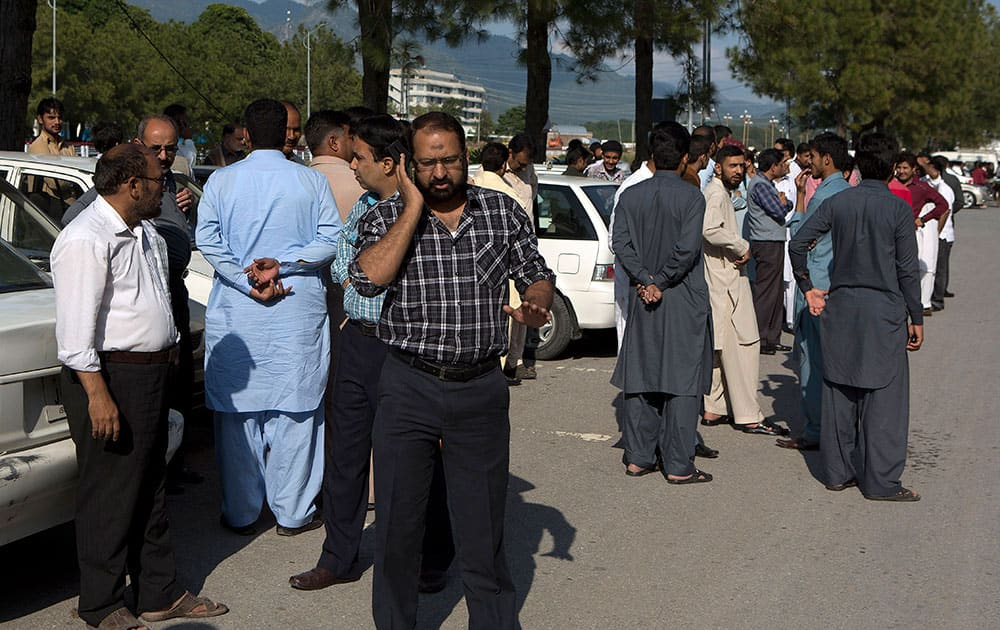 People stand outside their offices after a severe earthquake is felt in Islamabad, Pakistan. A powerful 7.7-magnitude earthquake in northern Afghanistan rocked cities across South Asia.