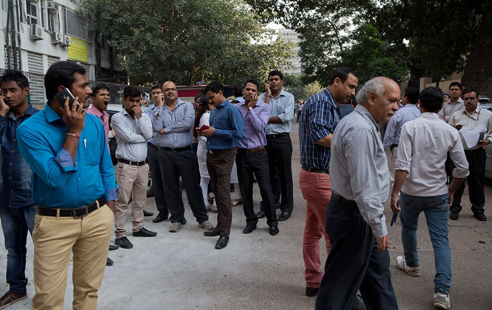 People stand after they rushed out of buildings as a strong tremor was felt in New Delhi.