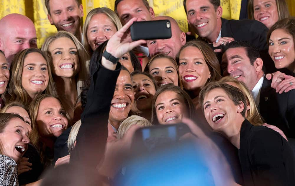 President Barack Obama poses for a selfie with the U.S. Womens National Soccer Team in the East Room of the White House in Washington.