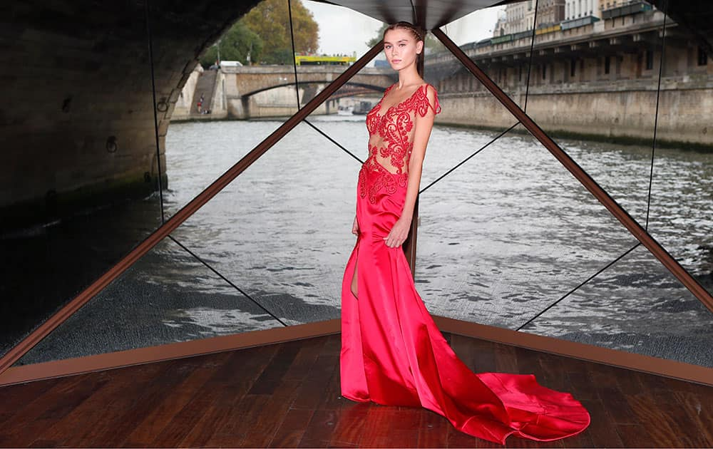 A model displays a creation as part of the Jessica Minh Anh Autumn Fashion Show on a floating catwalk set up in a boat cruising on the Seine river, in Paris.