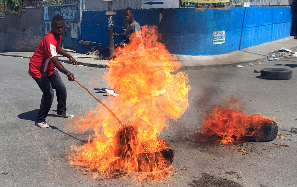 A protester supporter of presidential candidate Moise Jean-Charles, of the Platform Pitit Dessalines political party sets fire to a tire during a protest in Port-au-Prince, Haiti.