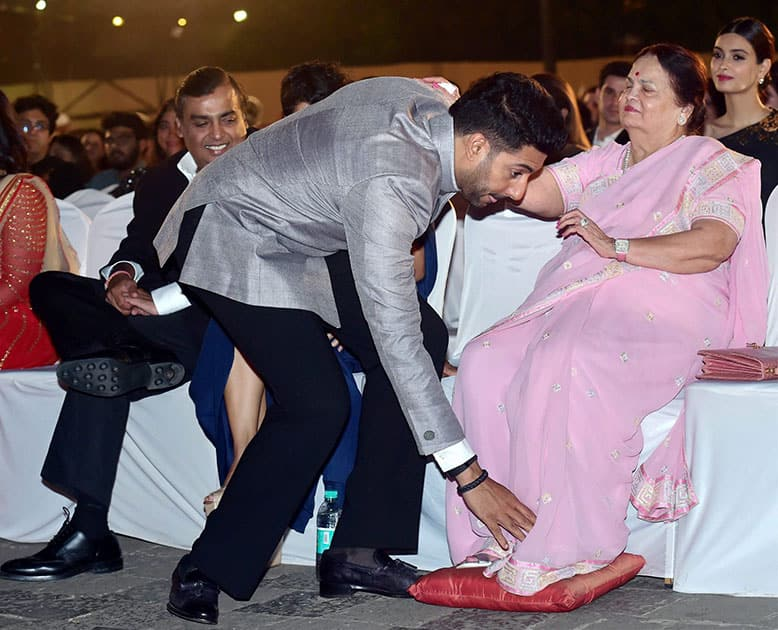 Industrialist Mukesh Ambani looks on as actor Abhishek Bachchan seeks blessing from Kokilaben Ambani during opening ceremony of 17th edition of Jio MAMI Mumbai Film Festival.