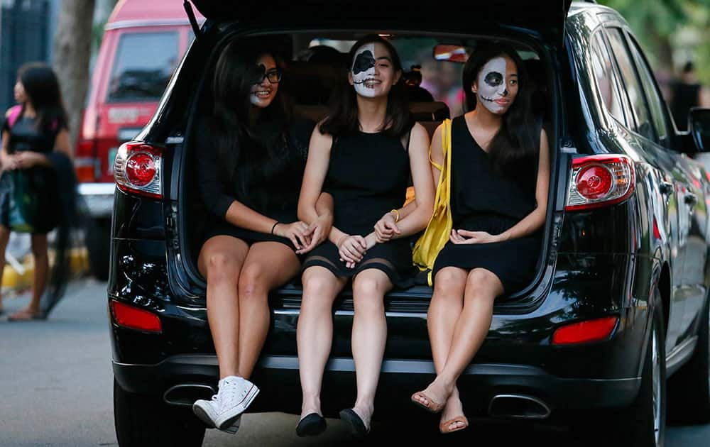 Girls, in their Halloween costumes, ride in the back of an SUV to collect candies and sweets known as 'trick or treat' on Halloween, the eve of the observance of All Saint's Day among Roman Catholics, at suburban Makati city east of Manila, Philippines.