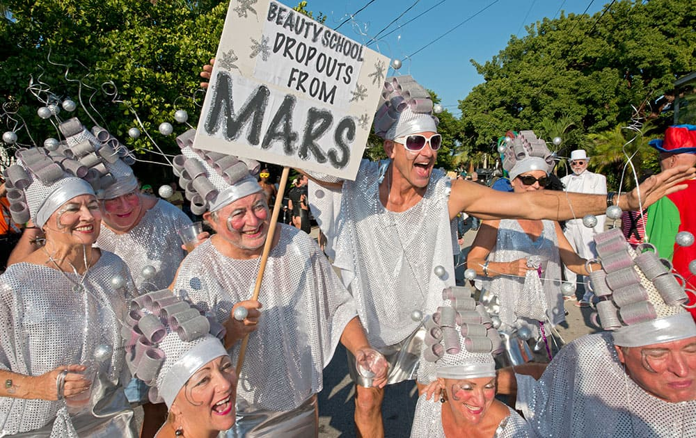 This photo provided by the Florida Keys News Bureau, space creatures walk down Fleming Street in Key West, Fla., during the Fantasy Fest Masquerade March.