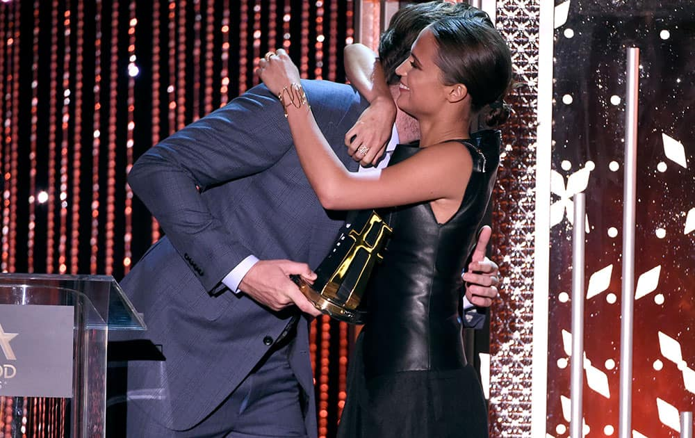 Armie Hammer, left, presents Alicia Vikander the Hollywood breakout actress award for