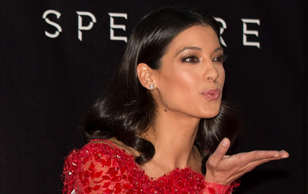 Actress Stephanie Sigman blows a kiss toward photographers as she walks the red carpet at the regional premiere of the latest James Bond film,