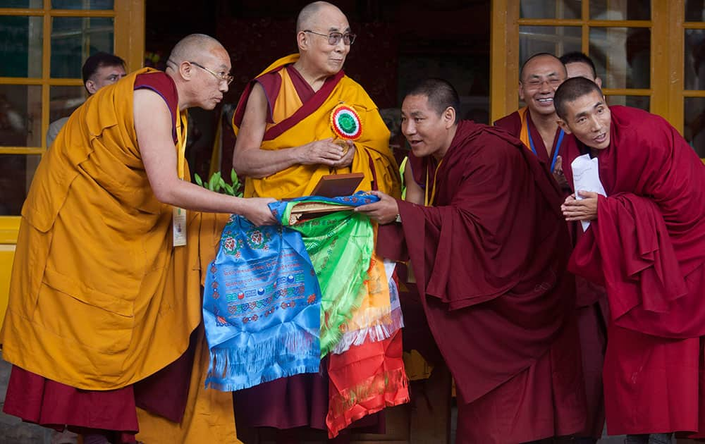 Tibetan spiritual leader the Dalai Lama receives a medal from a group of Tibetans as a token of their gratitude at the Tsuglakhang temple in Dharmsala.