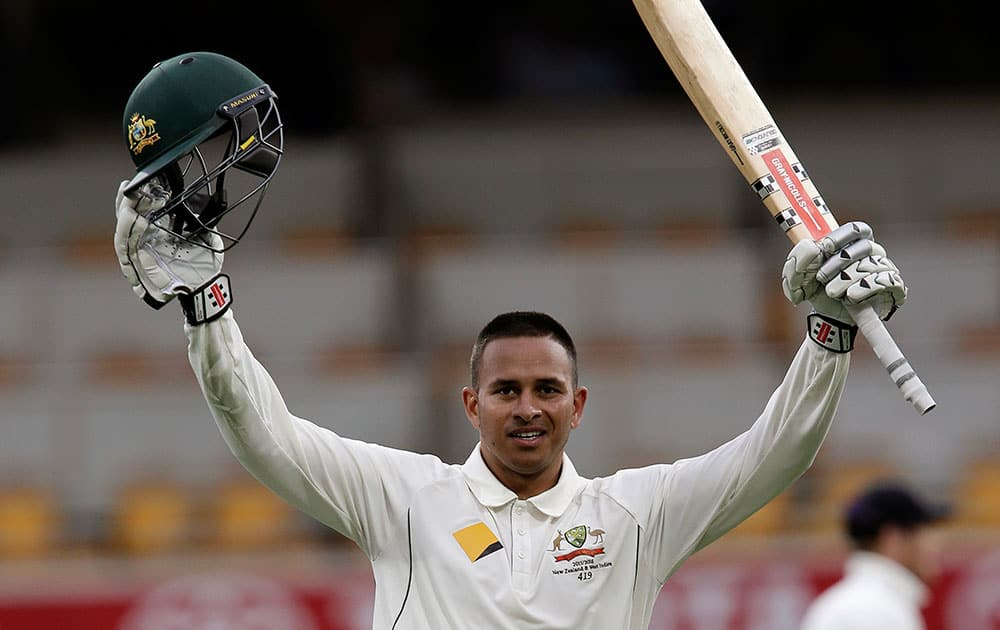 Australia's Usman Khawaja celebrates reaching 100 runs during play on day one of the first cricket test between Australia and New Zealand in Brisbane, Australia.