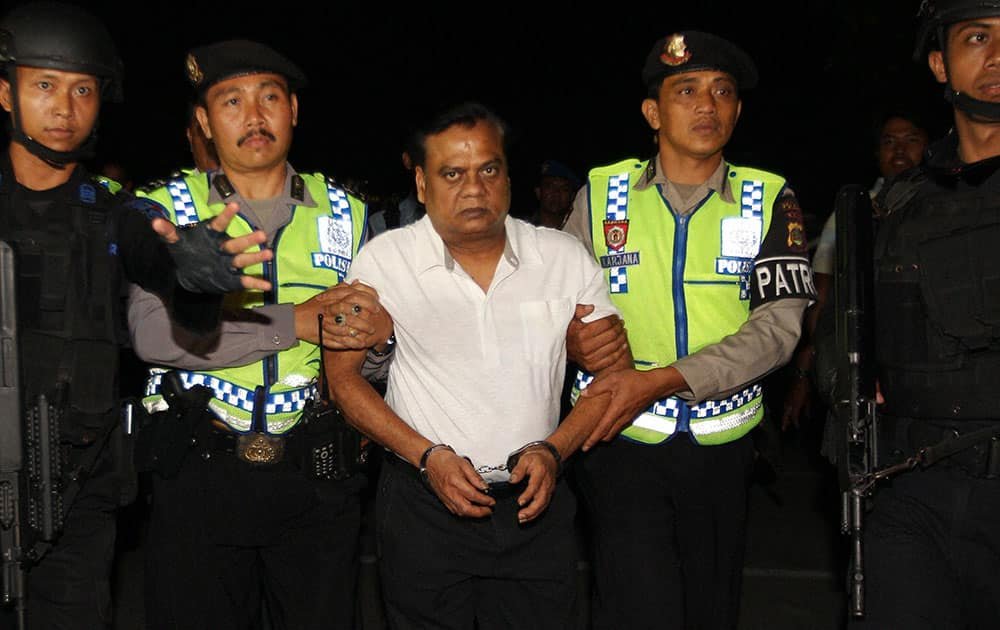 Indian fugitive Rajendra Sadashiv Nikalje, known in India as Chotta Rajan is escorted by police officers before being taken to Bali airport to be deported, Indonesia. The alleged organized crime boss, wanted for alleged involvement in several mafia killings and other major crimes in his homeland, was arrested Sunday after arriving at Balis airport from Sydney based on information from Interpol and Australian authorities.