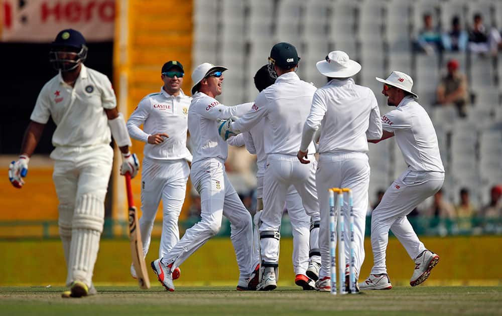 South African cricketers celebrate the dismissal of India's Cheteshwar Pujara during the first day of their first cricket test match in Mohali.