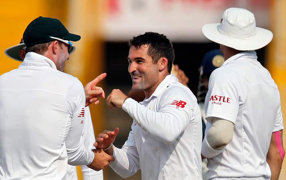 South Africa's Dean Elgar, center, celebrates the dismissal of India's Amit Mishra during the first day of their first cricket test match in Mohali.