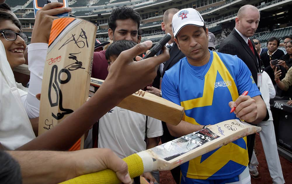 Retired cricketer Sachin Tendulkar autographs cricket bats during a clinic for kids ahead of the Cricket All-Stars series, at Citi Field in New York. The three-game series will be played in Major League Baseball stadiums in New York, Houston and Los Angeles.