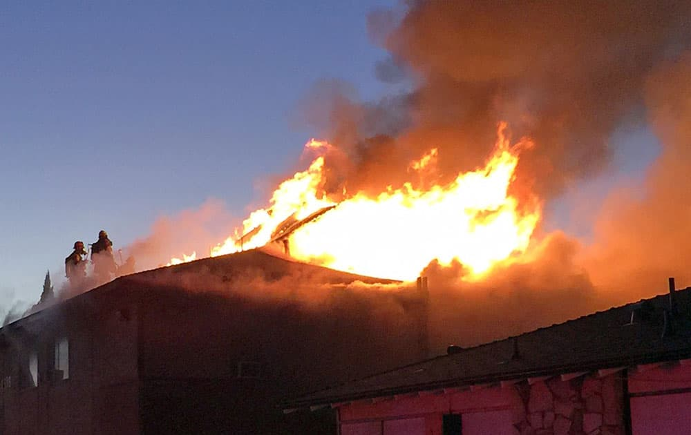 This photo provided by Anaheim Fire & Rescue, firefighters battle a blaze at two apartment complexes, in Anaheim, Calif.