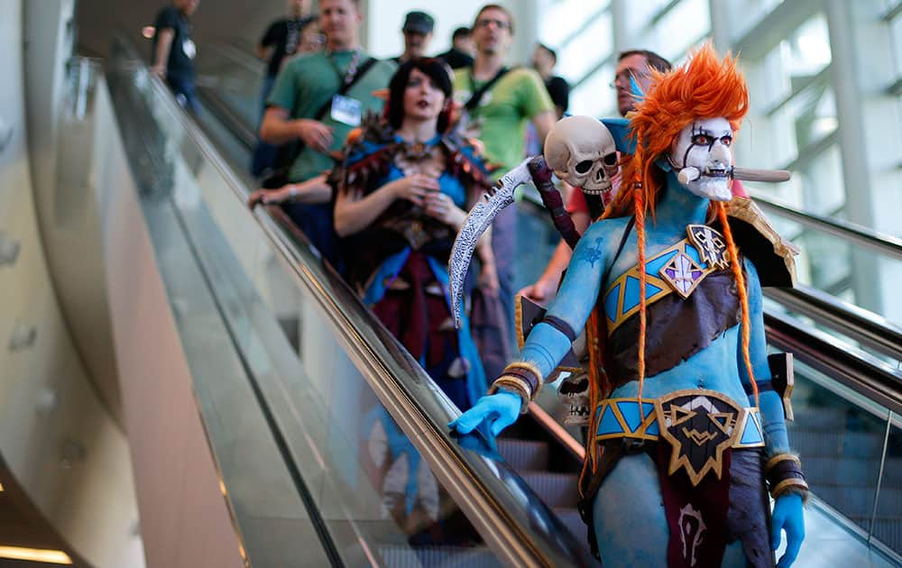 A woman dressed as Voljin from the video game World of Warcraft rides an escalator at the BlizzCon.