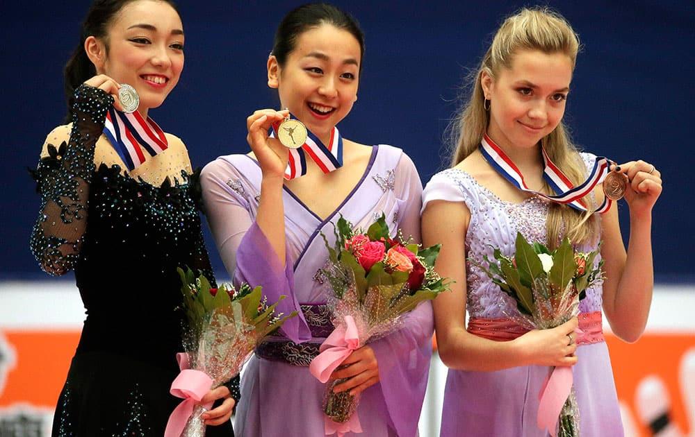 Silver medalist Rika Hongo of Japan, left, gold medalist Mao Asada of Japan, center, and bronze medalist Elena Radionova of Russia.