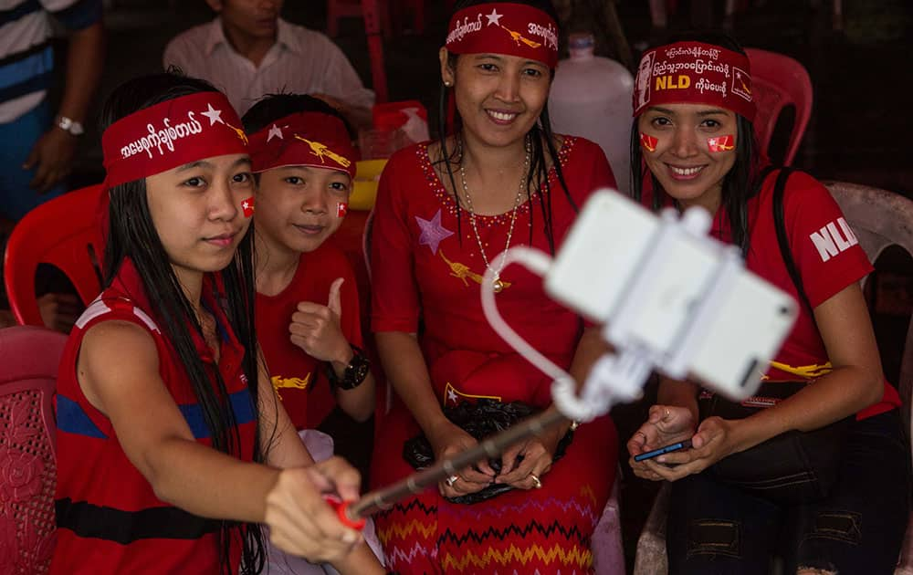 A group of opposition supporters take a selfie as hundreds of people gather outside the opposition party headquarters despite rain in Yangon, Myanmar.