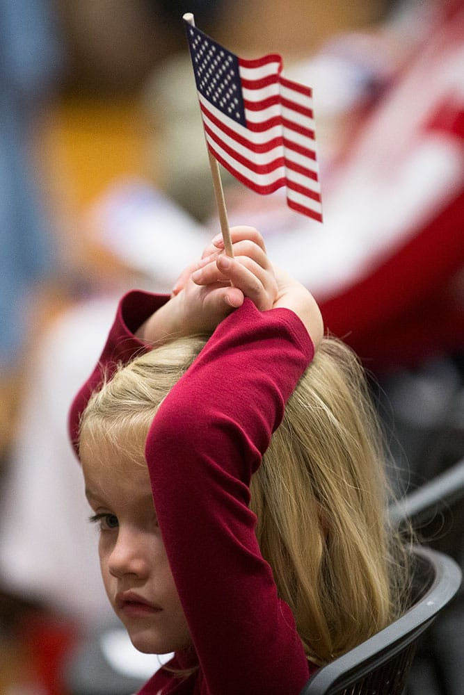 A child holds an American flag over her head during a Veterans Day ceremony in the Countryside YMCA's gymnasium in Lebanon, Ohio.