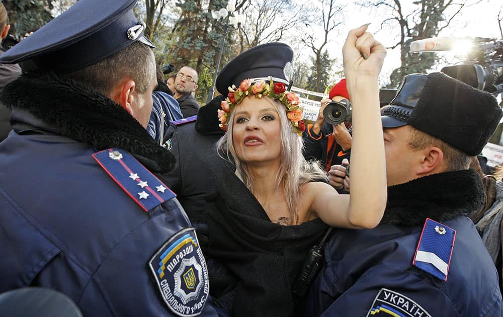Policemen detain a Femen womens movement activist in front of the parliament building in Kiev, Ukraine.