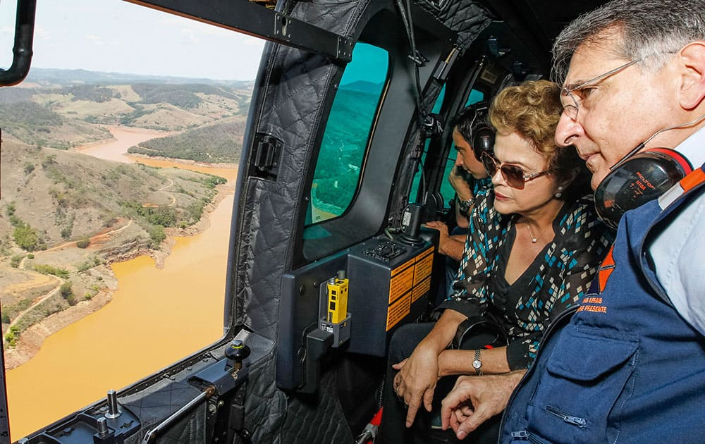 President Dilma Rousseff accompanied by Minas Gerais state Gov. Fernando Pimentel, looks out over the area of dam bursts at an iron ore mine, in the southeastern Brazilian state of Minas Gerais. Last week dam failures unleashed a deadly wave of viscous mud that all but erased a hamlet and contaminated a key river. Rousseff says the mining company, Samarco, will be made to pay for the cleanup.