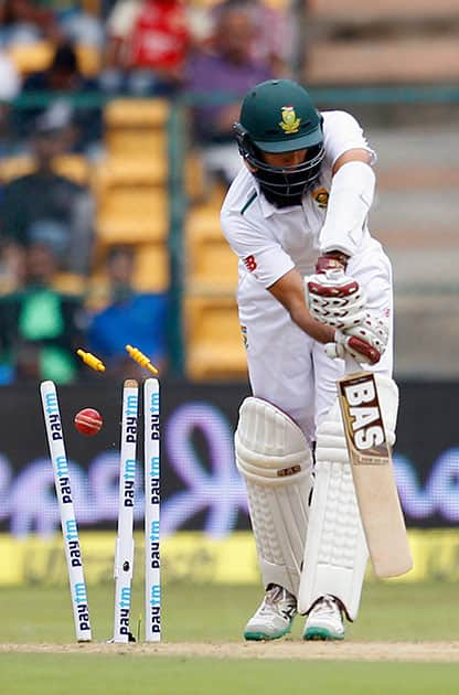 South Africa's captain Hashim Amla is bowled out by India's Varun Aaron during the first day of their second cricket test match in Bangalore.