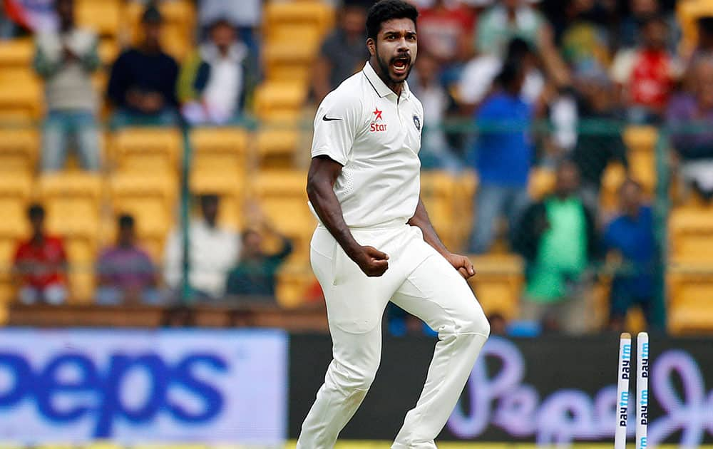 Varun Aaron celebrates the dismissal of South Africa's captain Hashim Amla during the first day of their second cricket test match in Bangalore.