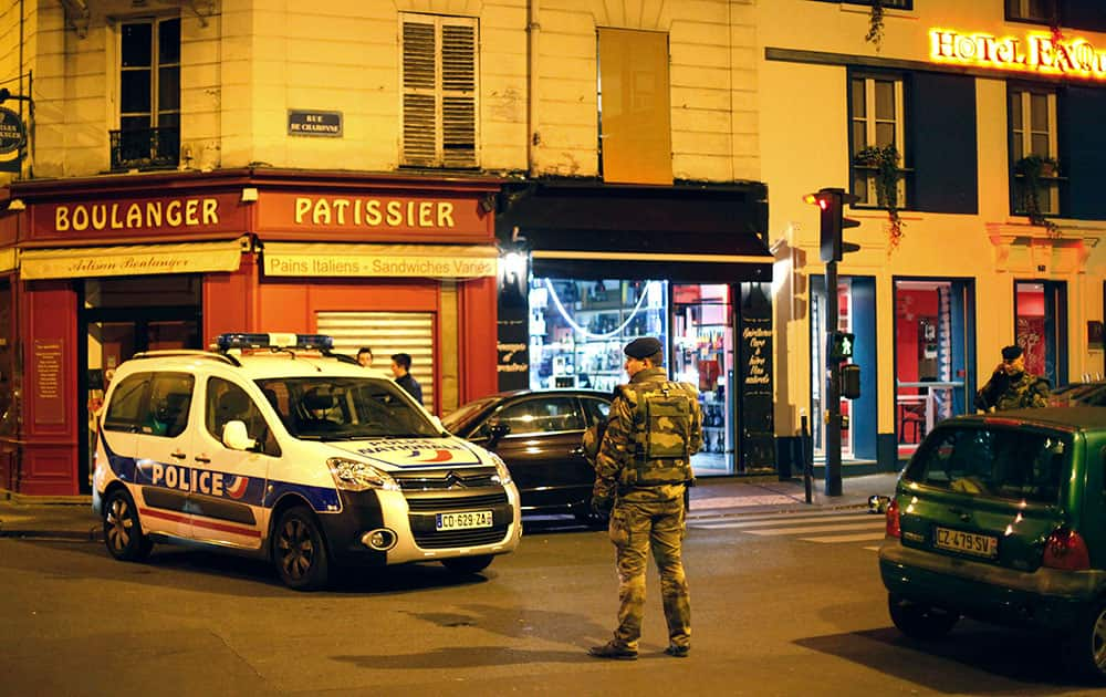 A French soldier stands in a street next to Rue de Charonne in Paris. A cafe on Rue de Charonne was one of the targeted sites in Friday's shootings. A series of attacks targeting young concert-goers, soccer fans and Parisians enjoying a Friday night out at popular nightspots killed over 100 people in the deadliest violence to strike France since World War II.