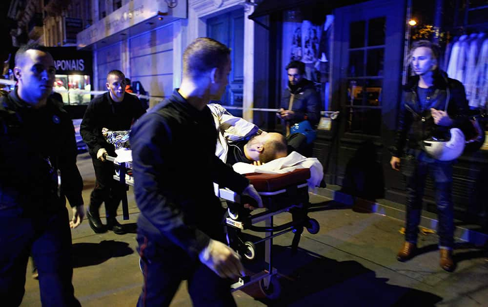 A person is being evacuated after a shooting, outside the Bataclan theater in Paris. A series of attacks targeting young concert-goers, soccer fans and Parisians enjoying a Friday night out at popular nightspots killed over 100 people in the deadliest violence to strike France since World War II.