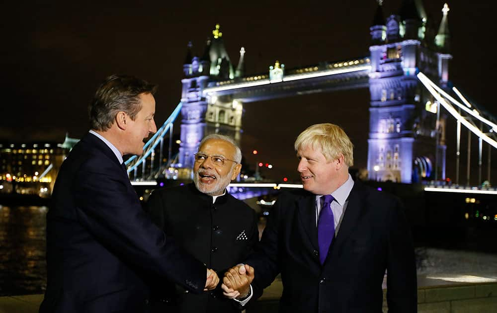 Britain's Prime Minister David Cameron with India's Prime Minister Narendra Modi and the Mayor of London Boris Johnson hold hands in front of Tower Bridge in London.