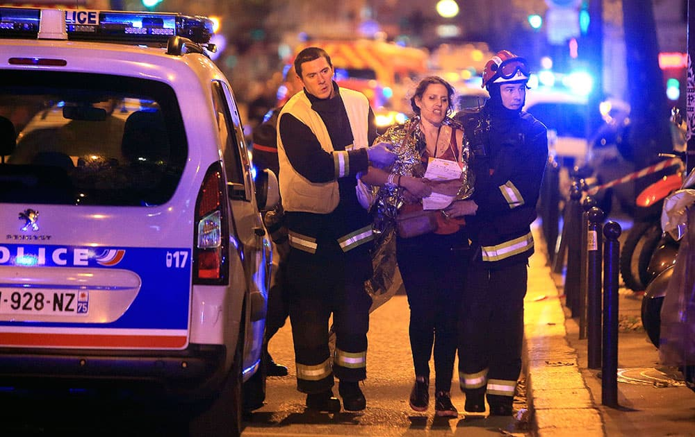 Rescue workers help a woman after a shooting, outside the Bataclan theater in Paris.