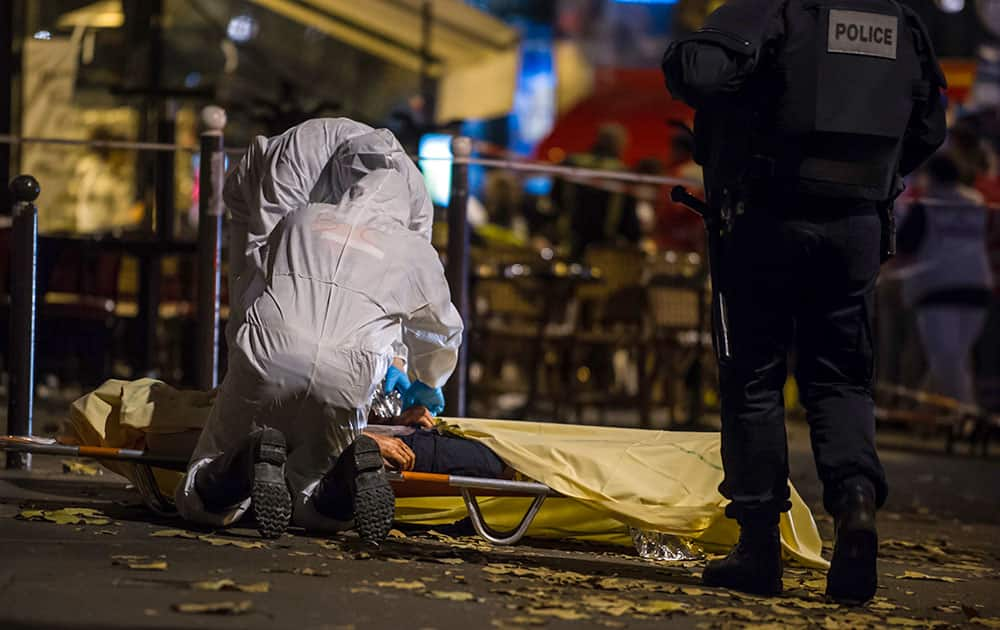 Investigating police officers inspect the lifeless body of a victim of a shooting attack outside the Bataclan concert hall in Paris, France.