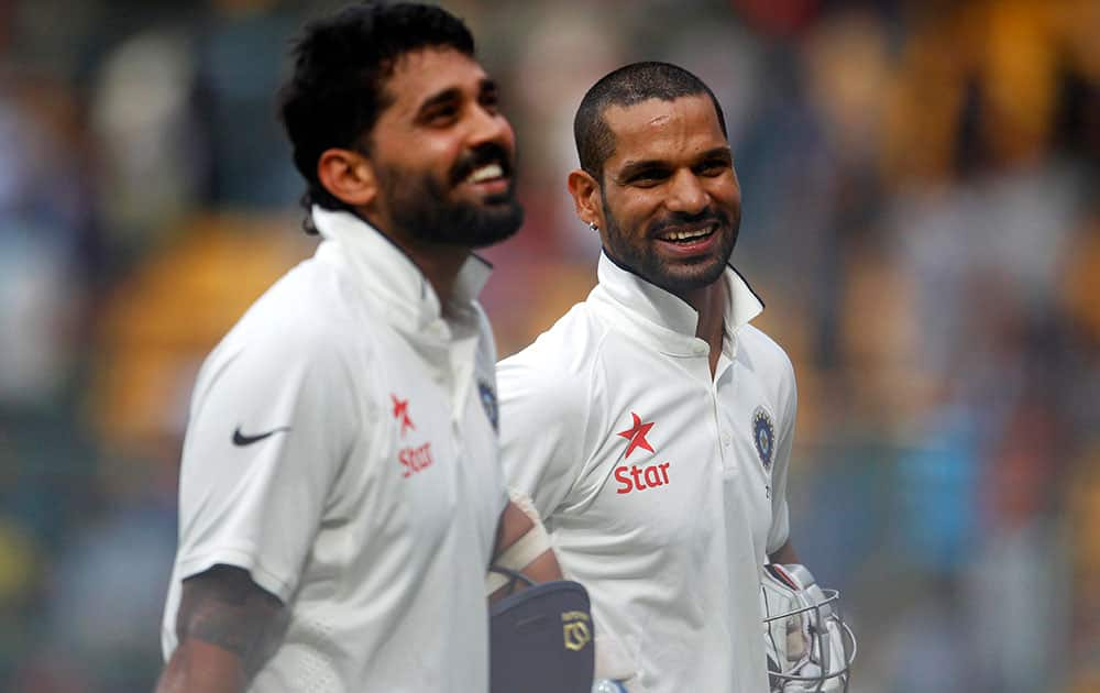 Murali Vijay and Shikhar Dhawan smile as they leave the ground at the end of the first day of their second cricket test match against South Africa in Bangalore.