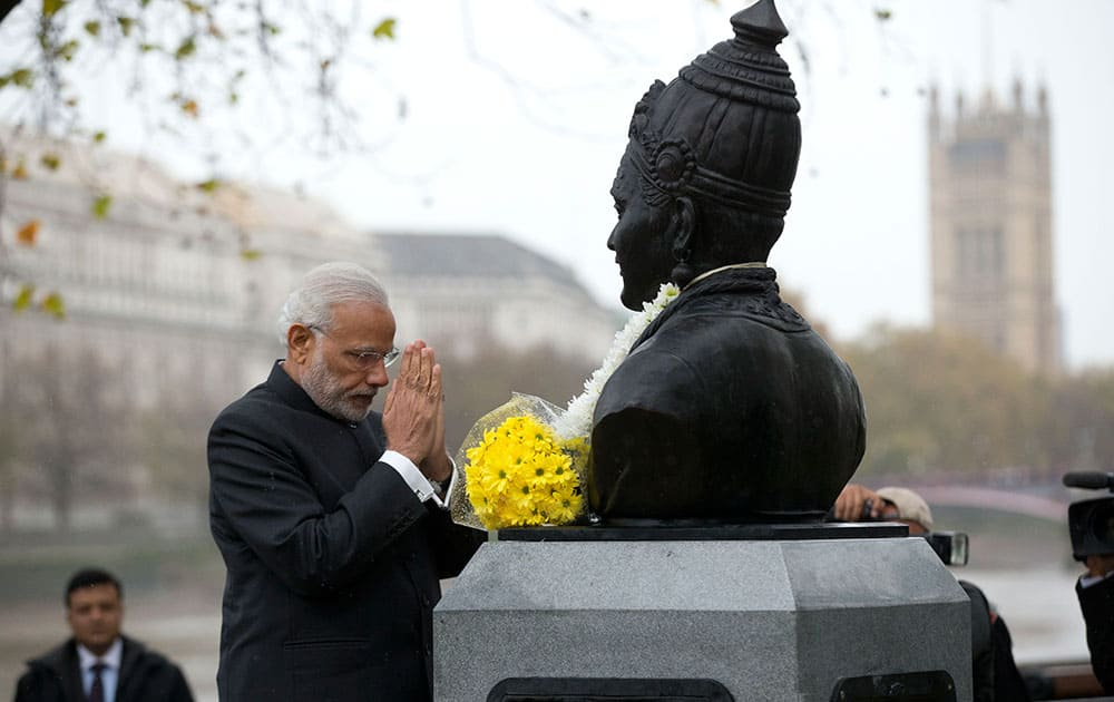 Indian Prime Minister Narendra Modi bows his head after unveiling a statue of 12th century Indian philosopher Basaveshwara, who was one of the pioneers of the idea of democracy, in London.