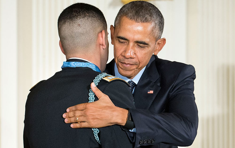 President Barack Obama and Florent Groberg embrace after Obama bestowed the nation's highest military honor, the Medal of Honor to Groberg, during a ceremony in the East Room of the White House in Washington.