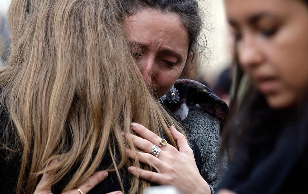 People hug each other as they gather in front of the French embassy in Rome.