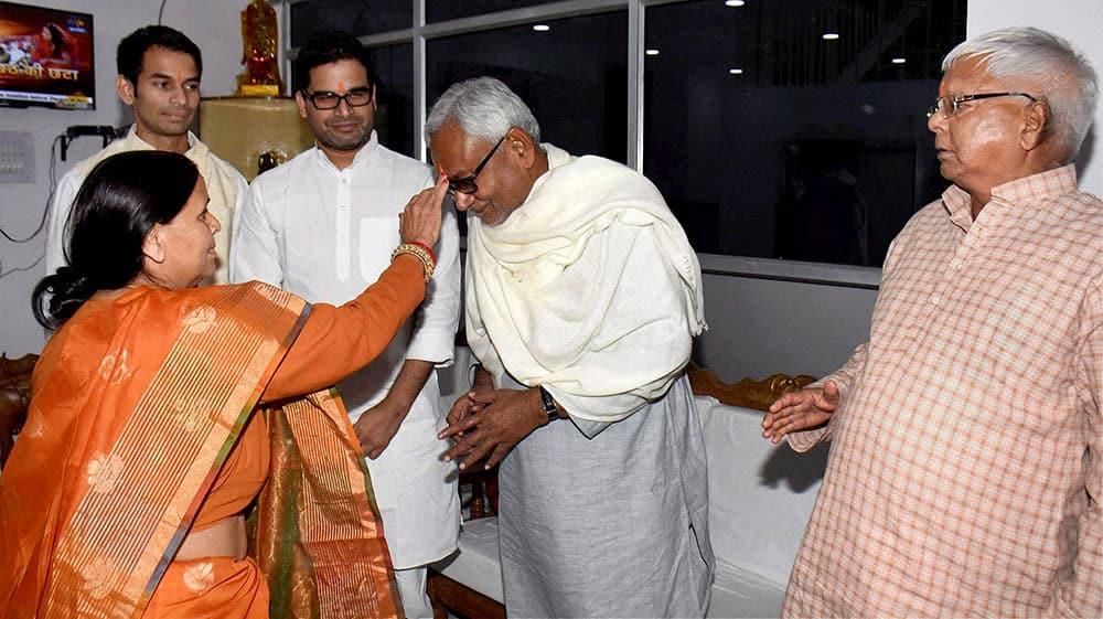 RJD leader Rabri Devi applying tikka to Bihar Chief Minister Nitish Kumar as RJD supremo Lalu Prasad looks on during Chhath festival in Patna.