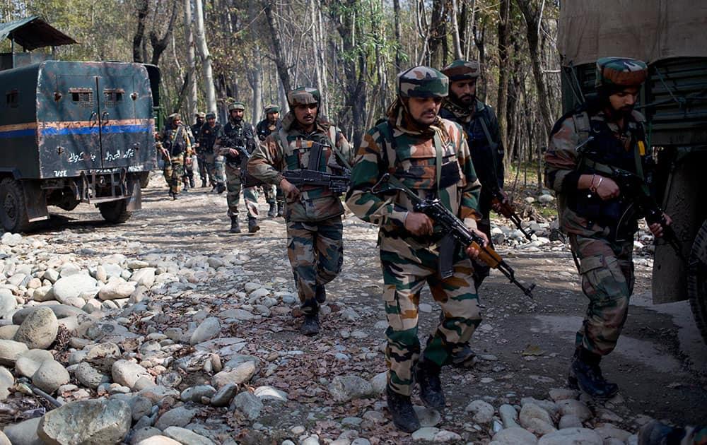 Army soldiers patrol near the site of a gunbattle with suspected rebels in Bungham village, northwest of Srinagar.