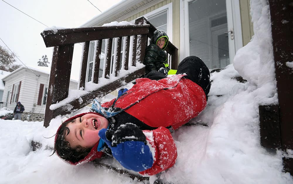 Luca Damato slides down packed snow on his stairs as Adam Stankus looks on while they play outside in Kenosha, Wis.