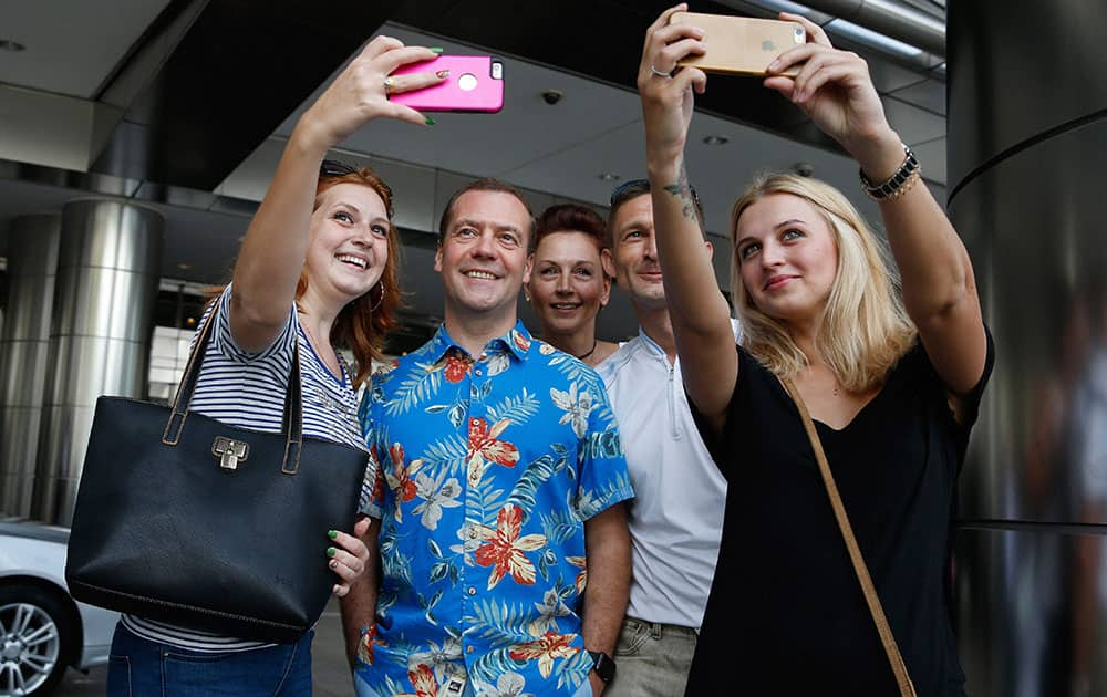 Russia's Prime Minister Dmitry Medvedev  poses for a photo with Russian and Ukrainian tourists after the East Asia Summit in Kuala Lumpur, Malaysia.