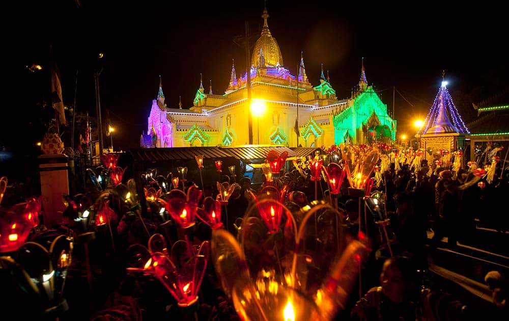 Ethnic Pa-O women march with paper lanterns during Tazaungdine Festival while Sulamani Pagoda is illuminated in Taunggyi, southern Shan State, Myanmar.