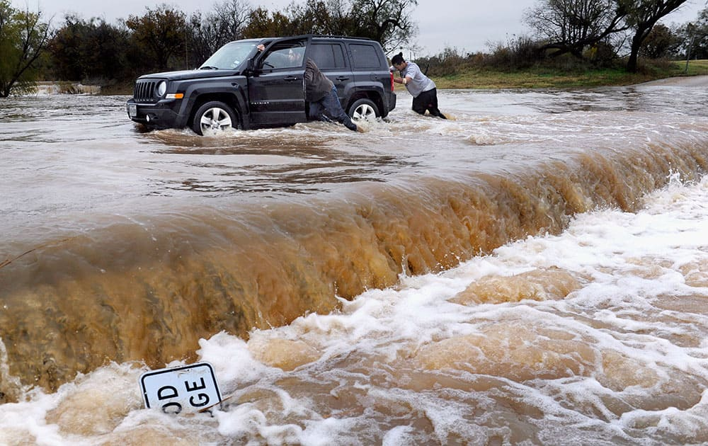 Two people push a vehicle out of high water at Cal Young Park in Abilene, Texas.