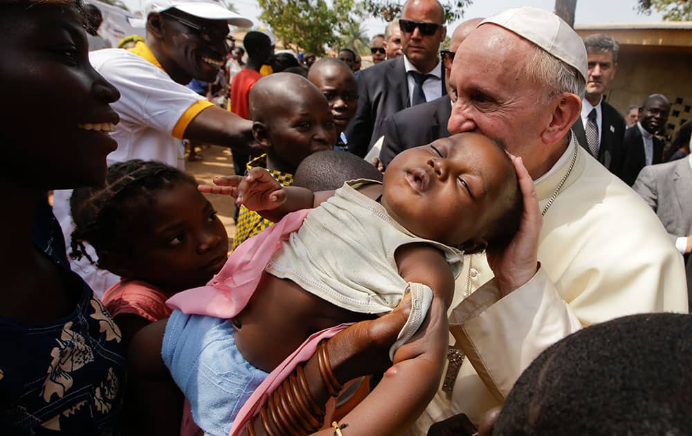Pope Francis caresses a baby as he visits a refugee camp, in Bangui, Central African Republic.