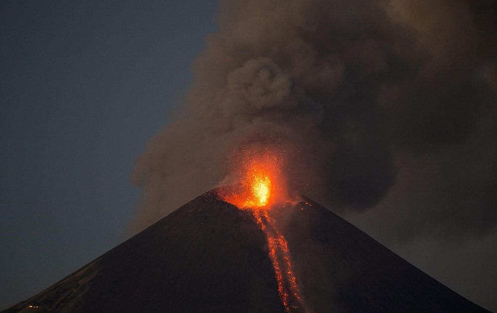 The Momotombo volcano spews a large plume of gas and ash as well as glowing rock, as seen from the rural community of Papalonal, in Leon, Nicaragua.