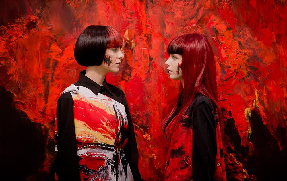 Models pose backdropped by a painting at the opening of an exhibition in Bucharest, Romania.